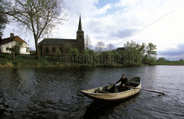 Millingerwaard the vicar of the church of Kekerdom the only church in Europa situated inside the dikes in a rowing boat on his way to the church