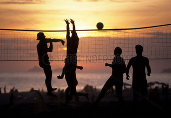 Beach volley-ball or beach volleyball at Ipanema beach  Rio de Janeiro  Brazil. An attacking move characterized by a forward thrust of the player who hits the ball with the open hand. Blockage  blockade. Sports  action  active  activities  activity  athle