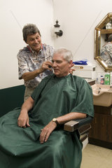Small town America old fashioned barber shop with customers and talking and laughing