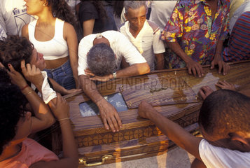 Funeral of victims of a slaughtering of workers in a shantytown by policemen. Rio de Janeiro  Brazil. Violence  human rights violation  suffering  black people  burial  coffin  pain  grief  sorrowful.