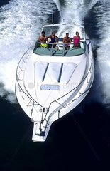 Couples running motor boat with wake and excitement as it moves thru water with speed from above aerial