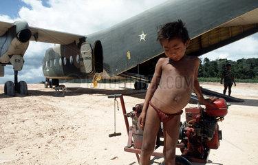 Amazon rainforest  Brazil. Indigenous People. Ianomami ( or Yanomami ) child at Brazilian Army base ( aircraft ). Multi-cultural relationship. Multi-ethnicity.