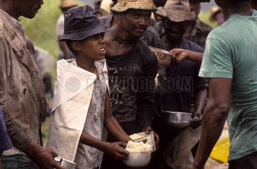 Latin America  Brazil. Debt-bondage at sugarcane plantation. Contemporary slavery  violation of human rights  child labor  poverty. Workers stand in line for meal in the rain. Sugarcane cutters.