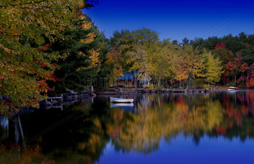Peaceful quiet scene of lake and small boat in Long Lake in Bridgton Maine in New England colorful scene with reflections