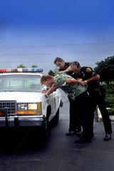 Police officers arrest a young man