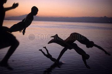 Kids jumping off a pier into the ocean  Rio de Janeiro  Brazil. Sunset  children__s play  fun.