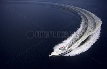 Graphic running motor boat with wake and excitement as it moves thru water with speed from above aerial with space all around the boat for copy