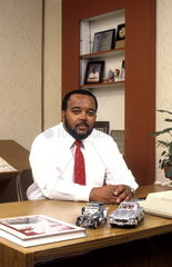 Professional black african american ethnic office business situation with man working at desk in modern office indoors