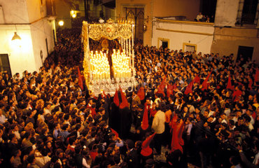 Jerez de la Frontera during the holy week of Eastern a hooded procession is carrying the statue of the Holy Mary through the night