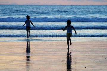 Indonesia: South-West coast of Bali . 2 Local Children playing in the Ocean at Kuta beach after the sun has set.