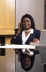 Attractive modern business woman at desk in great setting in office indoors at professional career