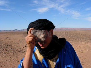 berber nomad is making fun and takes a picture with a stone which had a small hole in it  eastern sahara  near ouarzazate town  marocco