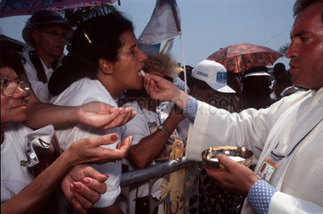 Religion in Latin America  Brazil. Outdoor mass  clerical. Catholicism. Women receives the Holy communion from priest. Religious fervour  faith.