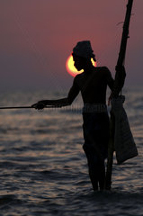 Weligama  traditional fishermen on stilts in the surf of the Indian Ocean off the south coast of the island