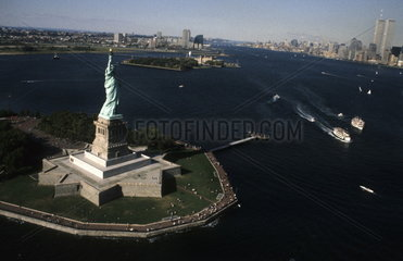 The beauty of the famous Statue of Liberty from a plane above the monument and the World Trade Centers in the background before 9/11 in New York City USA