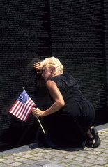 Widow mourning the loss after finding the name of her husband at the Vietnam Memorial Wall in Washington DC from the horrible war USA