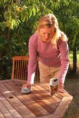 Femme entretenant une table d'extérieur en bois exotique