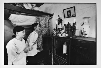Couple doing her morning prayers in their homes Vietnam