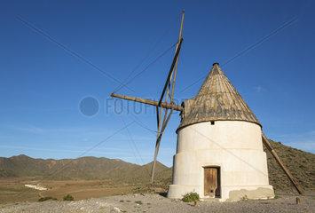The windmill Molino del Collado de los Genoveses and the abandoned farmhouse Cortijo de los Genoveses in the background. Nature Reserve Cabo de Gata-Nijar  Almeria province  Andalusia  Spain.