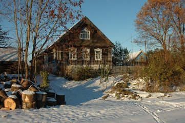 House out of wooden and wood cut under snow Russia