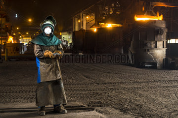 Worker holding ferronickel shot in front of molten furnaces. New Caledonia. Ferronickel contains 23 to 27% nickel. It is used to produce high quality stainless steel.