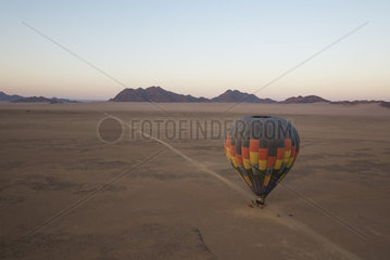 The passengers have boarded the basket and the hot-air balloon is almost ready for take-off. At dawn. Aerial view from a second balloon. Namib Desert  Kulala Wilderness Reserve  Namibia.