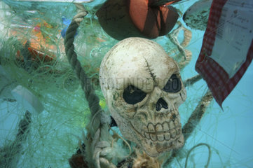 Concept image alluding to death caused by plastic garbage drifting in the oceans. Toy representing a skull in the middle of various plastic garbage floating in the ocean.. Kuwait  Persian Gulf