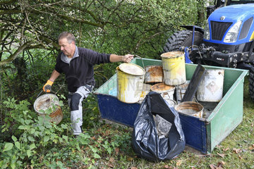 Collecting of a wild depot of paint cans in the ditch of a canal  France
