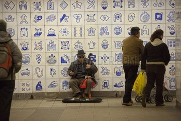 Musician begging in a corridor of the subway in New York