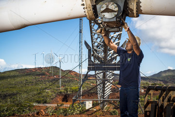 Worker performing the maintenance of a wind turbine. New Caledonia.