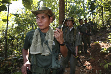 A KNLA soldier listening to a radio device near the border with Thailand. In Myanmar (Burma)  thousands of people have settled near the border as a result of oppression in their homeland. Around 200 Burmese displaced people have settled in La Per Her  a v