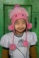 Burmese girl with her pompom cap  photographed in front of her classroom in the city of Nyuang U. On these cheeks  tanakha powder  to protect from the sun.