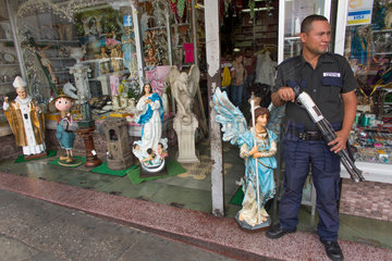 armed guard in front of a shop in guatamala city