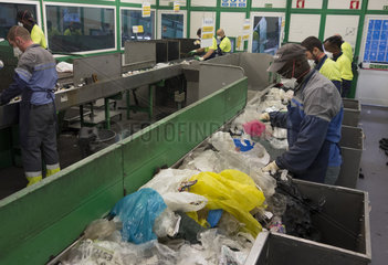 Employees of a waste facility on a conveyor belt sorting line. Manual sorting of plastic to to separate non-recyclable plastic PET objects. Some qualities of plastics can not be recycled and should be incinerated. PETs used in water bottles and juices instead can be recycled  for example  into garment fabrics. Portugal
