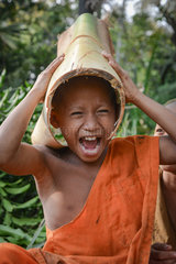 Cambodian monk in the province of Siem Reap playing with a banana trunk he puts on his head
