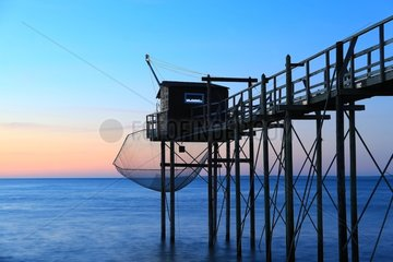 Pontoon and fishing shack liftnet at dusk - France
