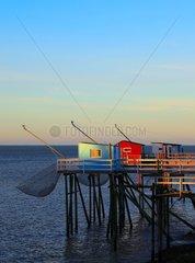 Pontoon and fishing shack liftnet at dusk - France