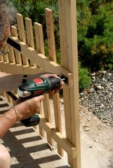 Man fixing child barrier with a drill in a garden