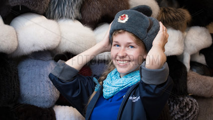 Russian teenager in a shop in Moscow trying on Russian hats