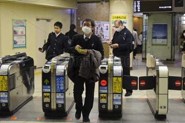 Passengers with mask in a rail station of Tokyo Japan