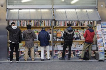 Reading in front of a news-stand in Tokyo Japan