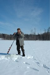 Man drilling the ice of a cold lake to fish Latvia