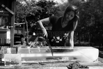 Young woman cutting ice in Cambodia