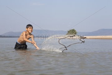Boy fishs with Casting-net fishing in the Mekong in Laos