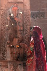 Woman praying before a statue Ganesh the elephant god-India