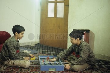 Boys iranniens playing on a carpet