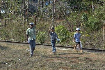 Enfants partant à l'école le long d'une voie ferrée en Inde