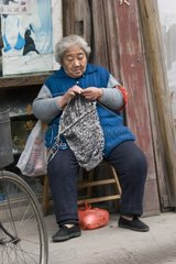 Woman knitting in a street of old Shanghai in China
