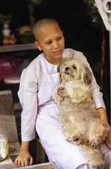 Nun sitting and holding a Pekinois on her knee Thaïland
