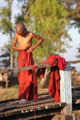 Young monk dressing after bathing Monastery Nyaungshwe